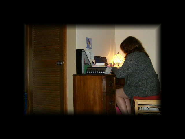 writer of blog sitting at a wooden desk with lamp on