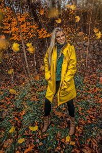Smiling woman in woods with falling leaves